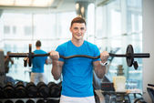Man doing exercises with barbell — Stock Photo