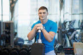 Man sits leaning on a dumbbell — Stock Photo