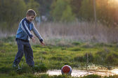Boy dropped the ball in a puddle and shouts — Stock Photo