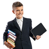 Schoolboy holding a tablet and books — Stock Photo