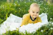 Little child lying on a diaper the grass — Stock Photo