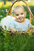 Small smiling child in sliders sitting a basket — Stock Photo