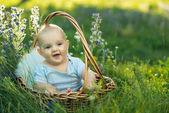 Small smiling child in sliders sitting a basket — ストック写真