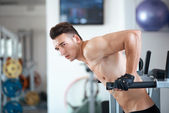 Man exercising in trainer for pectoral muscles — Foto de Stock