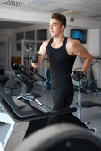 Athlete exercising on a stationary bike — Stock Photo