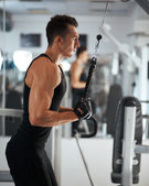 Man exercising in trainer for triceps muscles — Stock Photo
