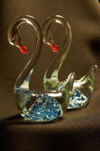 Swans.A pair of transparent glass figurines of swans on a black background — Stock Photo