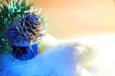 Christmas toy.Glass Christmas toy in the form of pine cone on the drum on the artificial Christmas tree branches — Stock Photo