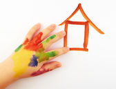 Child.A small child's hand soiled in paints draw a lodge — Stock Photo