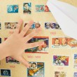 Child's hand on a background stamp collection on the theme of the cosmos - Stock Photo