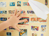 Child's hand on a background stamp collection on the theme of the cosmos — Stock Photo