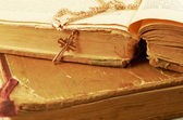 Ancient books.Gold chain with a cross on a background of old battered books — Stock Photo