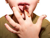 Child licks a chocolate glaze with your finger — Stock Photo