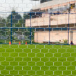 Goalpost net detail with green grass blur in background sports c — Stock Photo