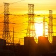 Silhouette of electric power lines and power station at sunset — Stockfoto