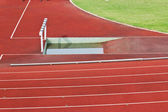 Hurdles on the red running track prepared for competition. — Stock fotografie