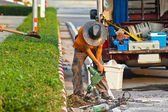 Road worker on a sidewalk with a jackhammer digging up concrete — Stock Photo