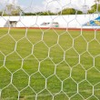 Football net on green grass background — Stock Photo