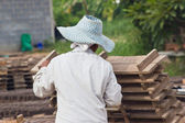 Woman laborer lifts the wood of Production of bricks in thailand — Stock Photo