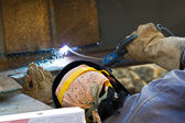 Outdoor worker with protective mask welding metal and sparks — Stock Photo