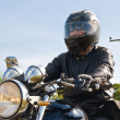 Stock Photo: View of a man with a motorcycle on a asphalt road.