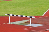 Hurdles on the red running track prepared for competition. — Stock Photo