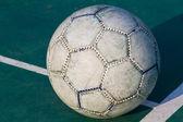 Old used football or soccer ball on cracked asphalt — Stock fotografie
