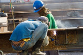 Outdoor worker with protective mask welding metal and sparks — Foto Stock