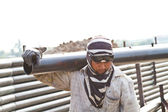 Construction worker carrying iron pipe — Stock Photo