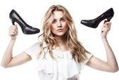 Fashion studio shot of shopping girl holding a black high heel s — Stock Photo