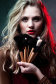 Portrait of beautiful woman with makeup brushes — Stock Photo