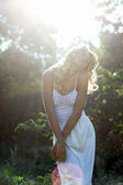 Beautiful girl in white dress walking on the meadow in summer day — Stock Photo