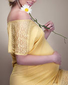 Pregnant woman holding spring flower — Stock Photo