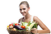 Happy young woman holding basket with vegetable — 图库照片