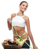 Happy young woman holding basket with vegetable — Stock Photo