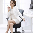 Businesswoman sitting in the office at the computer — Stock Photo