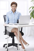 Businesswoman sitting at a laptop in the office — Stock Photo