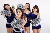 Vier asiatischen cheerleader posiert mit einer trophäe — Stockfoto