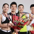 Group of young athletes holding trophy and flowers — Stock Photo