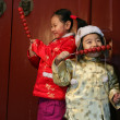 Stock Photo: Two chinese children dressed in traditional clothing eating cand