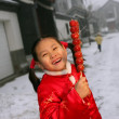 Stock Photo: One chinese girl dressed in traditional clothing holding candied