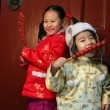 Two chinese children dressed in traditional clothing eating cand — Stock Photo
