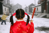Back view of two chinese children holding sugar-coated haws stan — Stock Photo