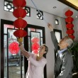 Chinese mature couple hanging lanterns — Stock Photo
