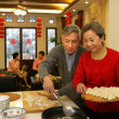 Chinese mature couple making chinese dumpling on New year's Eve — Stock Photo
