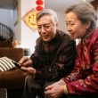 Chinese mature couple looking at a TV remote control — Stock Photo