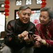 Chinese mature couple making a phone call — Stock Photo