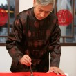 Chinese mature man writing Chinese couplet — Stock Photo