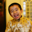 Stock Photo: One chinese boy dressed in traditional clothing looking at c