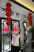 Chinese mature couple hanging lanterns — Stock Photo